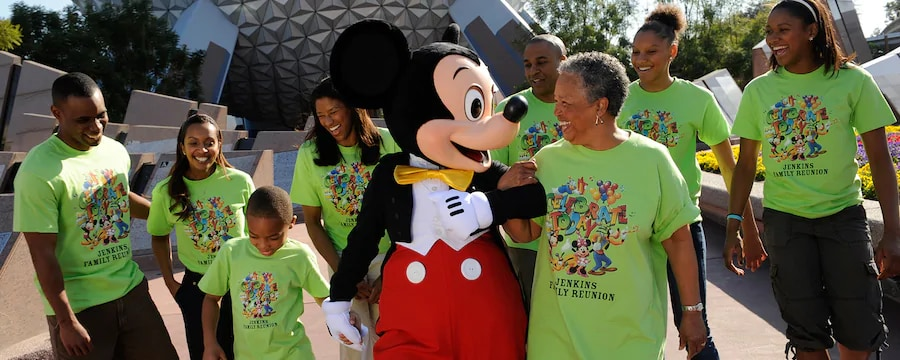 Several generations of a family, all in their reunion t-shirts, enjoy a walk with Mickey Mouse in front of Spaceship Earth at Epcot