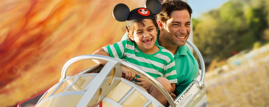 Un père, et son fils coiffé d'un chapeau à oreilles de Mickey, s'éclatent sur Astro Orbiter au parc Magic Kingdom du Walt Disney World Resort