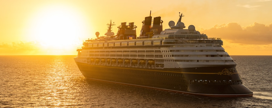 A Disney ship sailing on the ocean at sunset