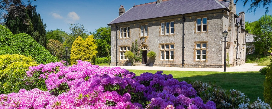 The main house and a colorful garden at Silverpoint Kentisbury Grange in England