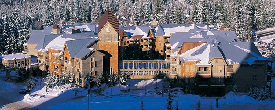 An aerial view of Club Intrawest — Whistler, with snow on ground, roof and treetops