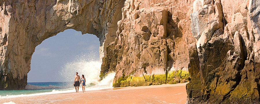 A couple holds hands while walking on the beach by El Arco in Cabo San Lucas, Mexico