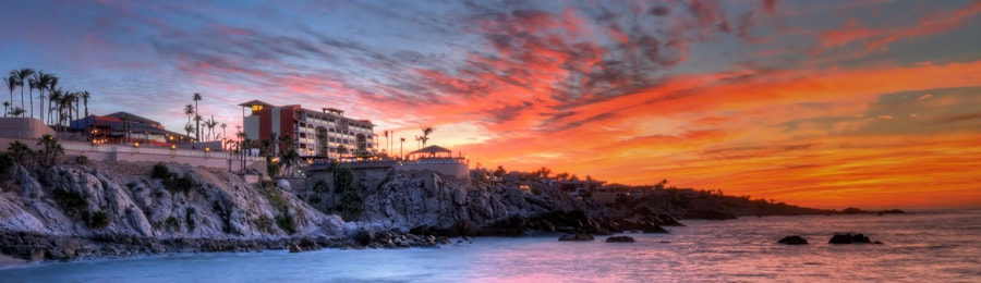 The exterior of Sirena de Mar by Welk Resorts along the rocky shoreline of Cabos San Lucas with a sunset backdrop
