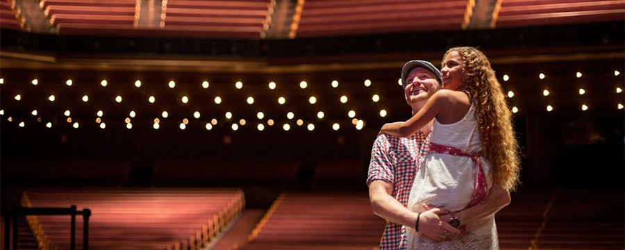 A man and his daughter in an empty Grand Ole Opry theater