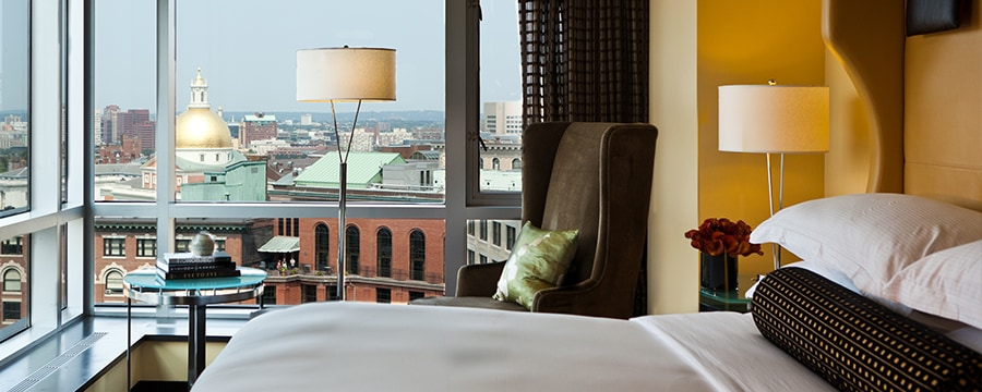 A guest room with large windows overlooking the city at Nine Zero Hotel in Boston