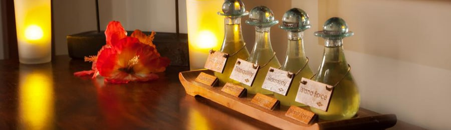 Four bottles of massage oils on a wood table beside 2 candles and a flower