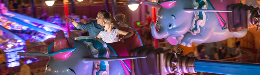 A mother and daughter on the Dumbo the Flying Elephant attraction at Magic Kingdom park