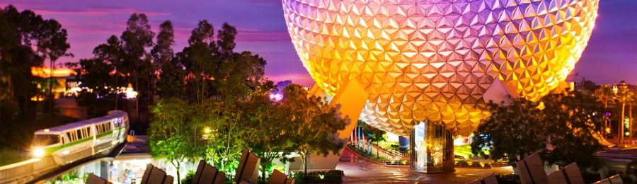 The Epcot Monorail cruising by Spaceship Earth at dusk
