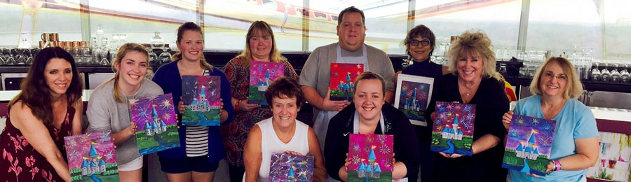 A group of 10 people, each holding a painting that depicts fireworks at Cinderella Castle