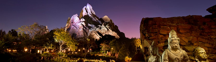 Nepalese stone sculptures beside Expedition Everest at dusk