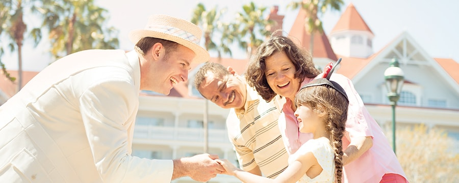 A Cast Member greets a family outside Disney's Grand Floridian Resort & Spa in Florida