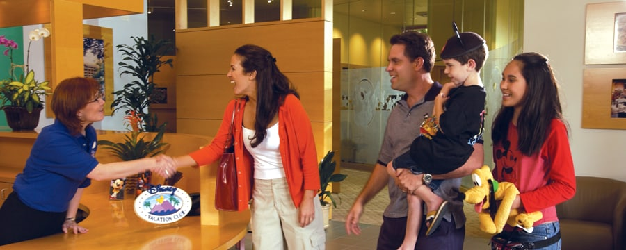 A Cast Member greets a family of 4 at a Disney Vacation Club Preview Centers