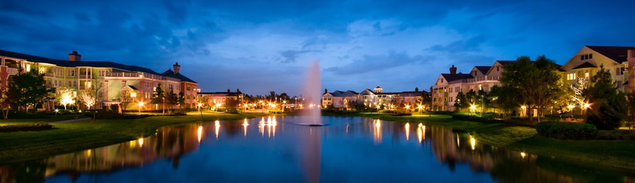 A lake with a fountain in the center, surrounded by several resort buildings