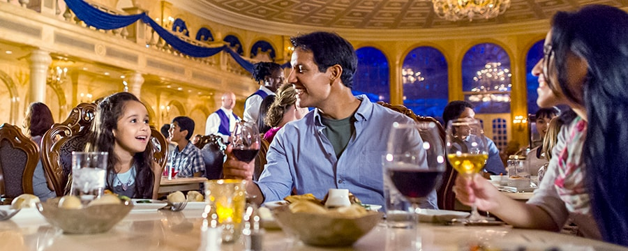 A young girl dining with her parents in The Grand Ballroom at Be Our Guest Restaurant