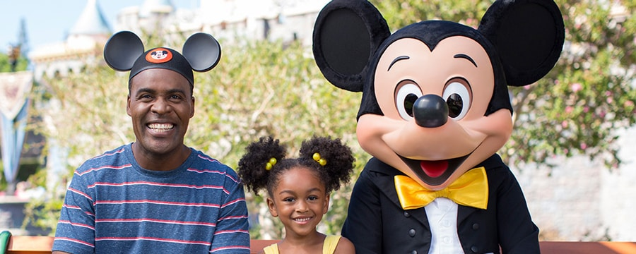 A dad wearing Mickey Ears and his daughter with her hair mimicking Mickey Ears pose with Mickey
