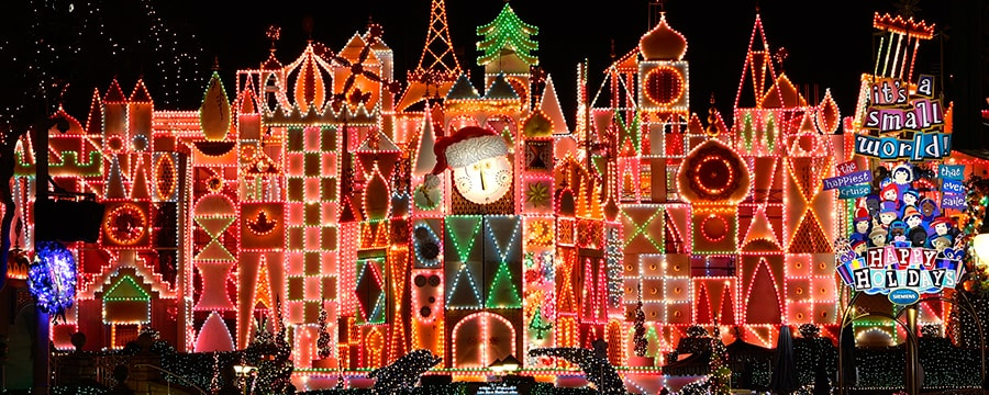 The illuminated, holiday-ready entrance to it's a small world at night