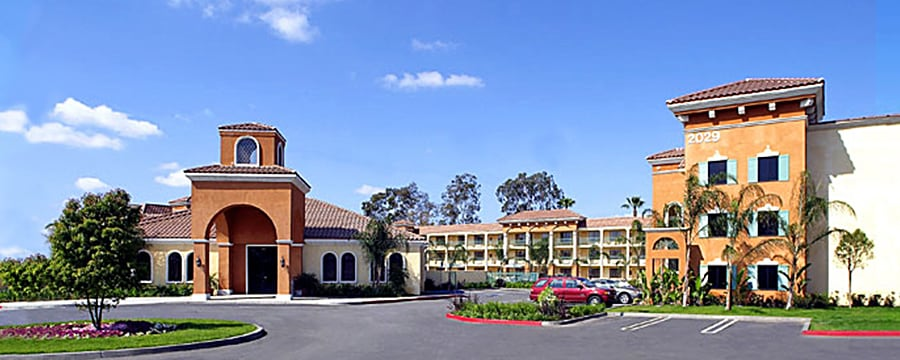 The entrance to Mission-style Cortona Inn & Suites Anaheim Resort