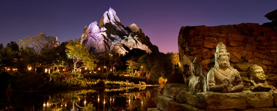 Asian statues and towering Forbidden Mountain at night in Disney's Animal Kingdom theme park