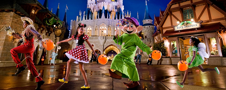 Children dressed as a scarecrow, Minnie Mouse and Tinker Bell march along with Dopey at Mickey's Not-So-Scary Halloween Party