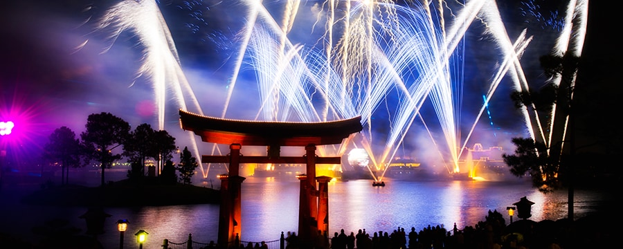 Fireworks light up the night sky above World Showcase Lagoon at Epcot, with Torii Gate at Japan Pavilion in the foreground