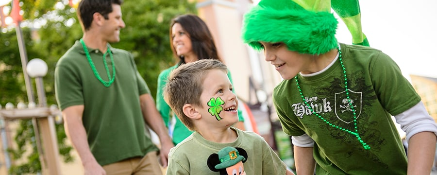 Two young Guests dressed for St. Patrick's Day laugh while walking directly ahead of their parents