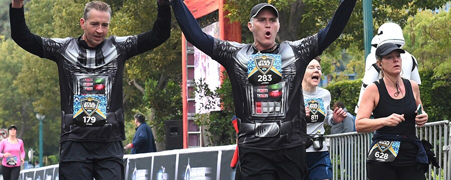 Two runners raise each others hands in victory as they cross the finish line together