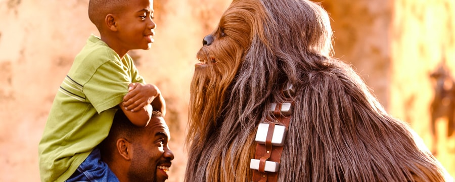 Little boy on his father's shoulders meets Star Wars Chewbacca face to face at Star Wars Weekends at Disney's Hollywood Studios