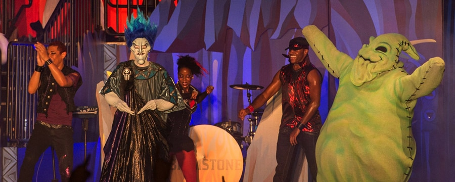 Disney villains Hades and Oogie Boogie perform on stage with the rock band Brimstone