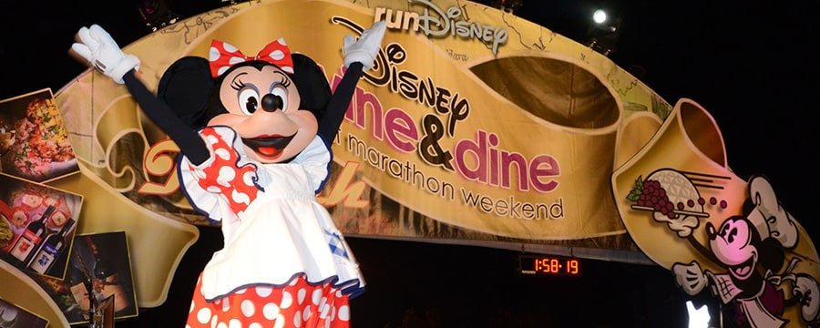 Minnie Mouse jumps in the air in celebration in front of a decorated archway with the Disney Wine & Dine half marathon weekend logo