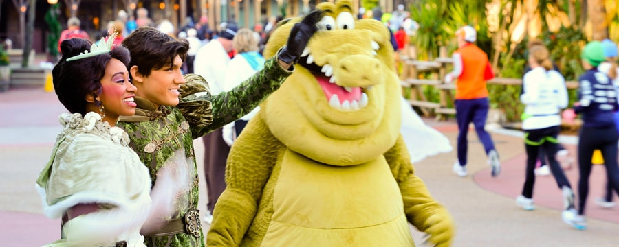 Characters Princess Tiana, Prince Naveen and alligator Louie cheer for runners