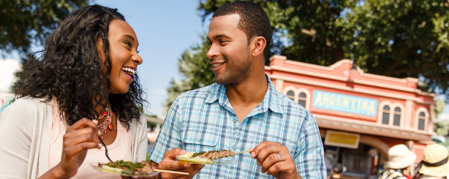 A young couple laugh while eating chicken kebabs in front of an Argentine restaurant