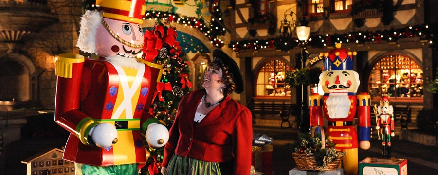 A woman smiling at a human-sized toy-soldier statue in an Epcot Holiday celebration