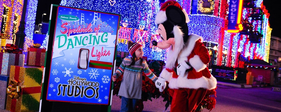 Character Mickey Mouse greets a little girl at the Spectacle of Dancing Lights