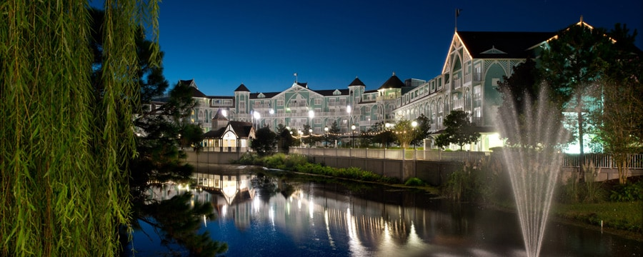 View from across a channel of Disney's Beach Club Villas, lit up at night