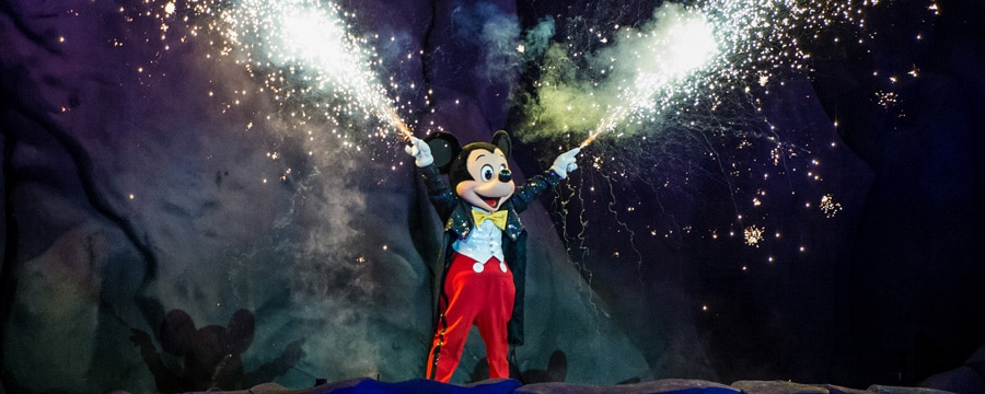 Sparks fly from Mickey Mouses hands during Fantasmic