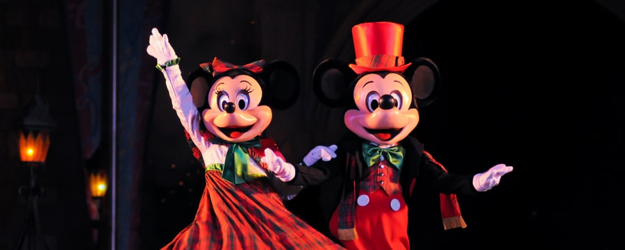 Mickey and Minnie dressed in their holiday finest, waving hello