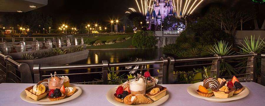 Three plates of desserts on a table and, in the background, fireworks over Cinderella Castle