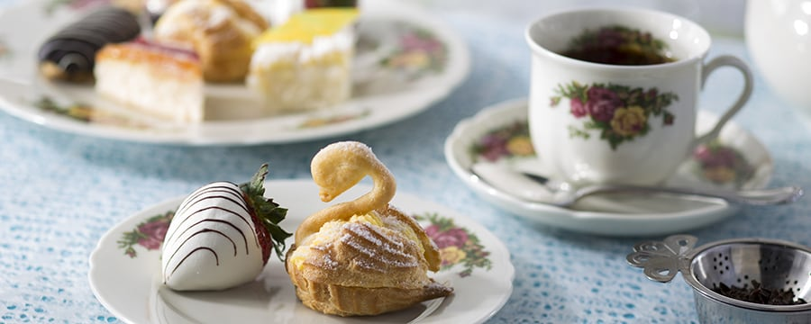 White chocolate-dipped strawberry, swan-shaped scones and black tea on floral English tea service china
