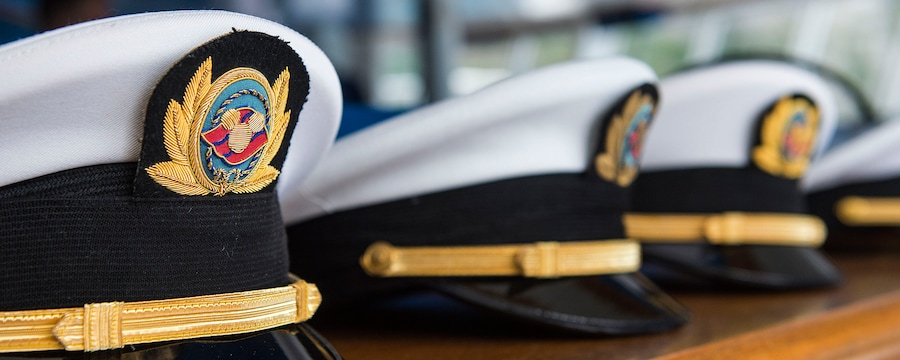 Captains' hats embroidered with the Disney Cruise Line logo sit in a row