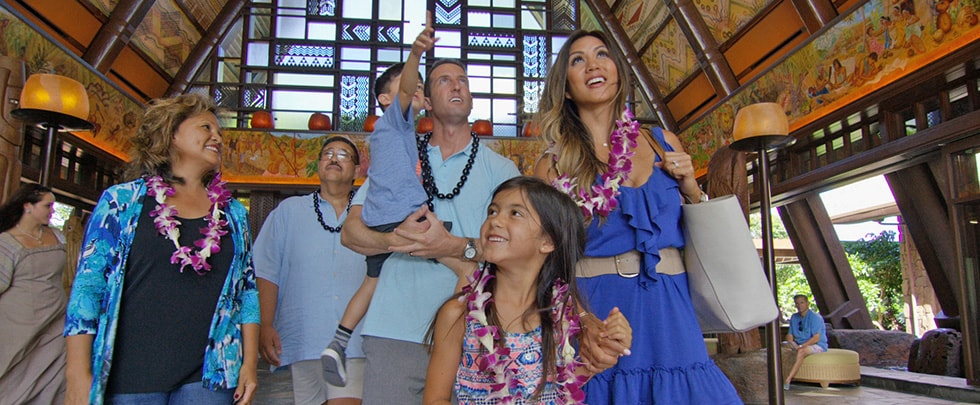 Two grandparents walk beside a couple and their 2 young children in the lobby at Aulani
