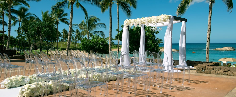 Weddings special events aulani hawaii resort spa rows of transparent chairs line an aisle leading to a seaside altar draped in white fabric junglespirit Images