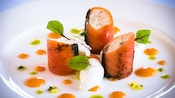 Smoked salmon strips wrapped around a creamy salmon mousse on a plate adorned with 3 kinds of sauce