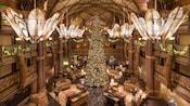An illuminated Christmas tree in the center of the lobby at Disney's Animal Kingdom Lodge