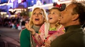 A smiling young girl and her parents marvel at holiday decorations
