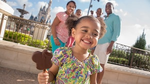 A smiling young girl enjoys a Mickey's premium ice cream bar as her family looks on