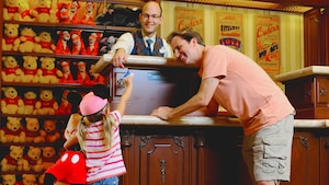 A young girl hands a Disney Gift Card to a cashier inside a shop as her smiling father looks on