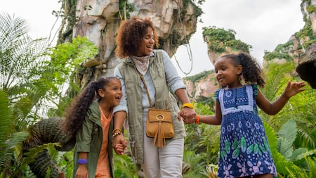 A mother holds hands with her 2 young daughters as they explore Pandora The World of Avatar together