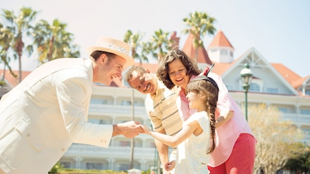 A Cast Member at Disney's Grand Floridian Resort and Spa shakes a young girl's hand as she stands outside with her grandparents