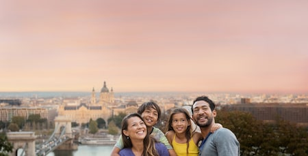 A mother and father pose with their son and daughter on a hillside overlooking a bridge, river and sprawling cityscape