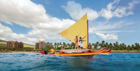 Aboard a motorized catamaran, two passengers stand and hold the rigging while others sit and enjoy the ride
